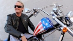 In this Friday, Oct. 23, 2009 file photo, Peter Fonda, poses atop a Harley-Davidson motorcycle in Glendale, Calif. (AP Photo/Chris Pizzello, File)