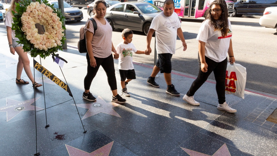 Tourists walk past flowers placed on the Walk of Fame star of Peter Fonda Friday, Aug. 16, 2019, in Los Angeles. (AP Photo/Damian Dovarganes)