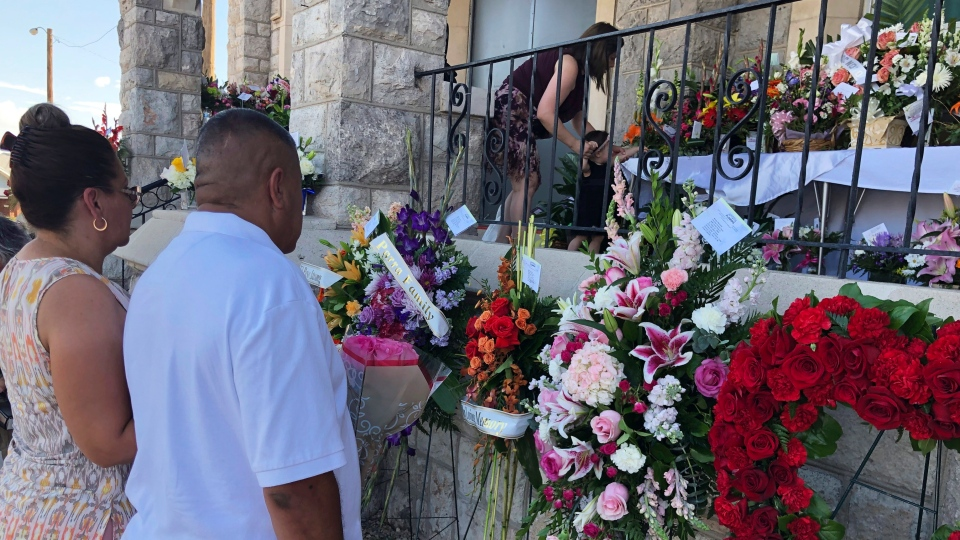 Mourners deliver flowers on Friday, Aug. 16, 2019, for the funeral in El Paso, Texas, of Margie Reckard, 63, who was killed by a gunman in a mass shooting earlier in the month. (AP Photo/Russell Contreras)