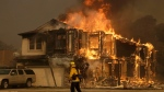 In this Oct. 9, 2017, file photo, a firefighter walks near a flaming house in Santa Rosa, Calif. A judge presiding over Pacific Gas and Electric's bankruptcy case is going to allow a state jury to decide whether the power company's equipment was the spark of the deadly 2017 fire. (AP Photo/Jeff Chiu, File)