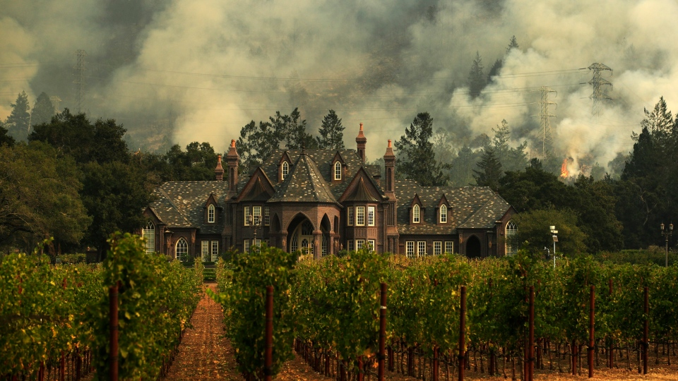 In this Oct. 14, 2017, file photo, the Tubbs wildfire burns behind a winery in Santa Rosa, Calif. (AP Photo/Jae C. Hong, File)