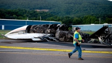 """The burned remains of a plane that was carrying NASCAR television analyst and former driver Dale Earnhardt Jr. lies near a runway Thursday, Aug. 15, 2019, in Elizabethton, Tenn. Officials said the Cessna Citation rolled off the end of a runway and caught fire after landing at Elizabethton Municipal Airport. Earnhardt's sister, Kelley EarnhardtMiller, tweeted that """"everyone is safe and has been taken to the hospital for further evaluation."""" (Calvin Mattheis/Knoxville News Sentinel via AP)"""