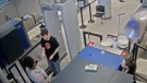 Security video captures the moment an unnamed security work at Greater Rochester International Airport in New York hands passenger Neal Strassner a handwritten note after he passes through a metal detector. (CNN)
