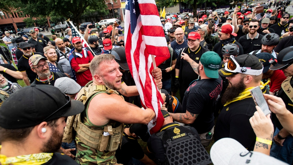 "Joseph Oakman and fellow Proud Boys plant a flag in Tom McCall Waterfront Park during an ""End Domestic Terrorism"" rally in Portland, Ore., on Saturday, Aug. 17, 2019. (AP Photo/Noah Berger)"