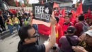 A Hong Kong anti-extradition bill protester holds up a sign in front of pro-China counter-protesters during opposing rallies in Vancouver, on Saturday August 17, 2019. THE CANADIAN PRESS/Darryl Dyck