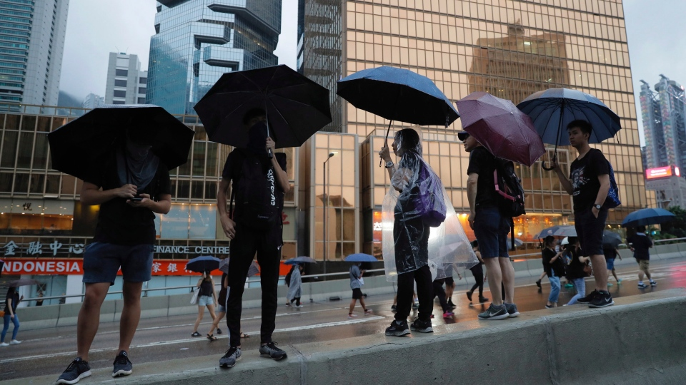 Protesters march in the rain in Hong Kong, Sunday, Aug. 18, 2019. (AP Photo/Kin Cheung)