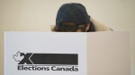 A woman marks her ballot behind a privacy barrier in the riding of Vaudreuil-Soulanges, west of Montreal, on October 19, 2015. An Elections Canada official warned some environment charities that any group that says the climate crisis is a real emergency could be considered partisan. THE CANADIAN PRESS IMAGES/Graham Hughes