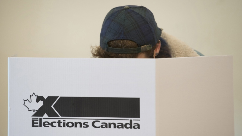 A woman marks her ballot behind a privacy barrier in the riding of Vaudreuil-Soulanges, west of Montreal, on October 19, 2015.THE CANADIAN PRESS IMAGES/Graham Hughes