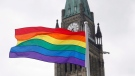In this file photo, the pride flag flies in front of the Peace Tower on Parliament Hill after a flag raising ceremony in Ottawa on Wednesday, June 20, 2018. (THE CANADIAN PRESS/ Patrick Doyle)
