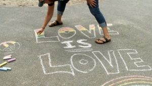 A person draws in chalk at a Pride event on Sunday in Ottawa.