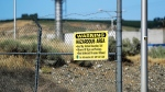 In this Wednesday, Aug. 14, 2019 photo, a sign at the Hanford Nuclear Reservation warns of possible hazards in the soil there along the Columbia River near Richland, Wash. (AP Photo/Elaine Thompson)