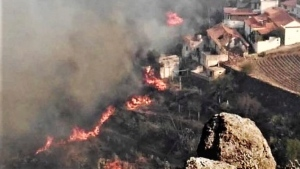 In this photo issued by Cabildo de Gran Canaria, flames from a forest fire burn close to houses in El Rincon, Tejeda on the Spanish Gran Canaria island on Sunday Aug. 18, 2019. (Cabildo de Gran Canaria Via AP)