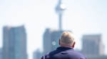 Ontario Premier Doug Ford faces the Toronto skyline as he attends the opening remarks before the start of Toronto's Caribbean Carnival festival on Saturday, Aug. 3, 2019. THE CANADIAN PRESS/Chris Young