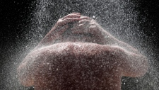 A man takes a cold shower in order to refresh himself at Ada Ciganlija lake in the Serbian capital, Belgrade, Wednesday, June 26, 2019. (AP Photo/Darko Vojinovic)