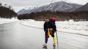 Venezuelan Yeslie Aranda, 57, walks on Route 3 between Tolhuin and Ushuaia, Argentina, Saturday, Aug. 17, 2019. Aranda left his hometown of San Cristobal in the southeastern state of Táchira last year with a backpack, $30 in his pocket and an aluminum prosthesis that enabled him to negotiate the continent's rugged roads. (AP Photo/Luján Agusti)