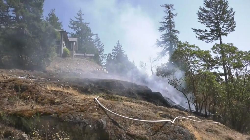 Sooke fire crews battle brush blaze metres from home