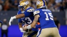 Winnipeg Blue Bombers quarterback Matt Nichols (15) hands off to Andrew Harris (33) against BC Lions during the second half of CFL action in Winnipeg Thursday, August 15, 2019. (The Canadian Press/John Woods)