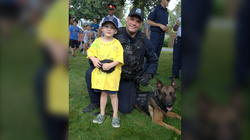 Four year old Sam Cargill is seen with a Durham Regional Police officer. (Colin Williamson/CTV News Toronto)
