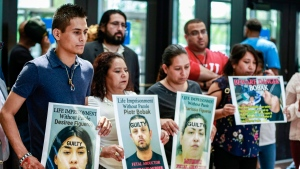 In this file image, Yovani Lopez, left, father of Yovanny Jadiel Lopez and husband of Marlen Ochoa-Lopez, holds a placard during a news conference at the Leighton Criminal Court building in Chicago, Wednesday, June 26, 2019. (AP Photo/Amr Alfiky)