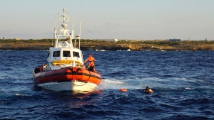 A man who threw himself in the water from the Open Arms vessel, is intercepted by the Italian Coast guards as he tried to swim to the island of Lampedusa, southern Italy, Tuesday, Aug. 20, 2019. (AP Photo/Francisco Gentico)