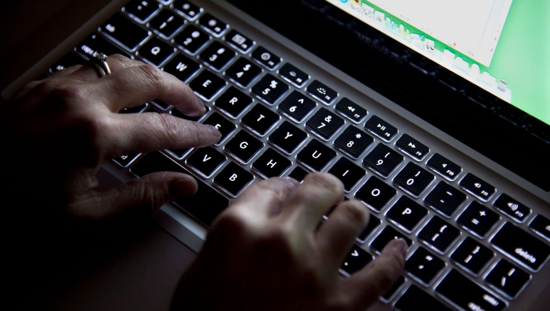 A deputy judge is calling for passage of clear laws on which innocent party should bear responsibility for financial losses related to cyberfraud. A woman uses her computer key board to type while surfing the internet in North Vancouver, B.C., Wednesday, Dec. 19, 2012. THE CANADIAN PRESS/Jonathan Hayward