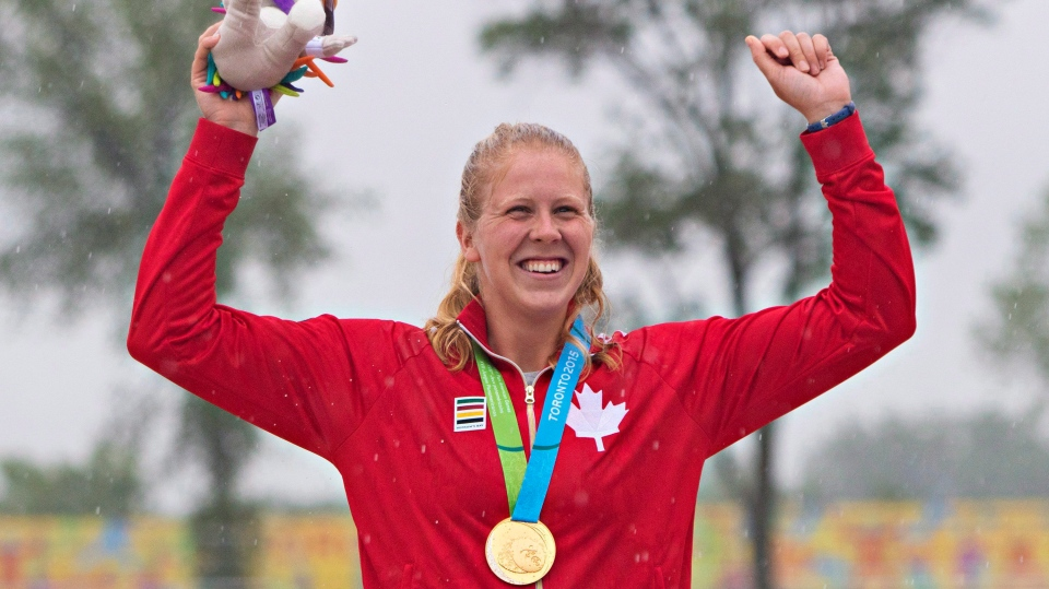 Canada's Laurence Vincent Lapointe accepts her gold medal for the women's C1 200m canoe race during a rainy medal ceremony at the 2015 Pan Am Games in Welland, Ont., Tuesday, July 14, 2015. (THE CANADIAN PRESS / Aaron Lynett)