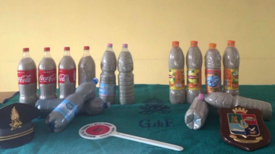 This picture taken on Aug. 16, 2019 by the Finance Police of the Sardinian port of Porto Torres, Italy, shows 14 plastic bottles of sand seized from a French couple in the trunk of the couple's car. (Italian Finance Police via AP)