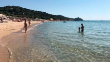 This June 29, 2019 photo made available Tuesday, Aug. 20, 2019 shows people enjoying the white sand and pristine waters of Chia beach, on the Italian island of Sardinia, Italy. (AP Photo/Karl A.Ritter)