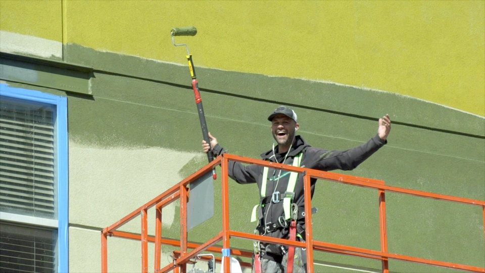 Calgary painter David Brunning is all smiles as he works on a mural in the Beltline.