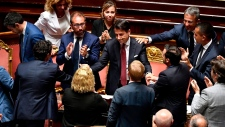 Italian Premier Giuseppe Conte, center, is congratulated at the end of his address to the Senate, in Rome, Tuesday, Aug. 20, 2019. Italian Premier Giuseppe Conte has told senators he's handing in his resignation because his right-wing coalition partner has yanked its support for the populist government. (Ettore Ferrari / ANSA via AP)