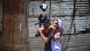 In this photo taken July 25, 2019, 15-year-old Karelys Herrera holds her baby after giving him a bath behind her home in the Caucaguita neighborhood on the outskirts of Caracas, Venezuela. (AP Photo/Ariana Cubillos)