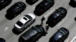 In this July 2, 2019, file photo men cross the street between vehicles waiting for a green light on East Lombard Street in downtown Baltimore. (AP Photo/Julio Cortez, File)