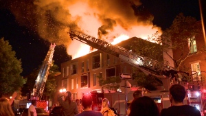 Flames leap from the roof of an apartment building on Rouville St. near Prefontaine St. in Montreal on Aug. 21, 2019 (CTV Montreal/Cosmo Santamaria)