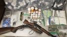 A large quantity of drugs, cash and two firearms are displayed after a police raid in Angus on Thurs., Aug. 15, 2019 (OPP)