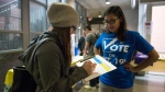Rabbia Ashraf, vice-president internal at the Continuing Education Students' Association of Ryerson (CESAR) talks to 2nd year student Katey Agnitsch about voting on Oct, 7, 2015. THE CANADIAN PRESS/Marta Iwanek