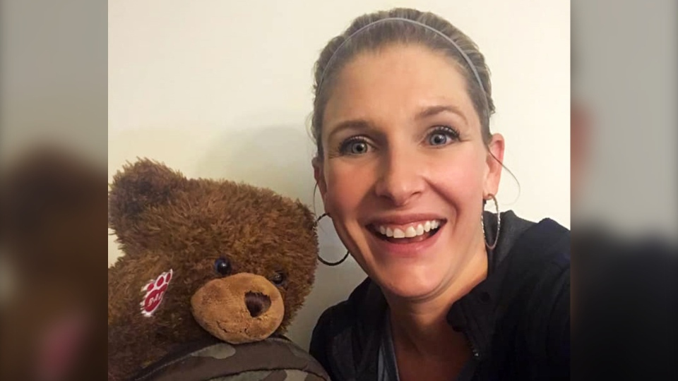 Heidi Erickson poses for a photo with Duncan MacMaster's lost teddy bear.