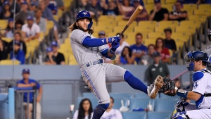 Toronto Blue Jays' Bo Bichette spins around on a swinging strike, next toLos Angeles Dodgers catcher Will Smith during the 10th inning of a baseball game Wednesday, Aug. 21, 2019, in Los Angeles. (AP Photo/Mark J. Terrill)
