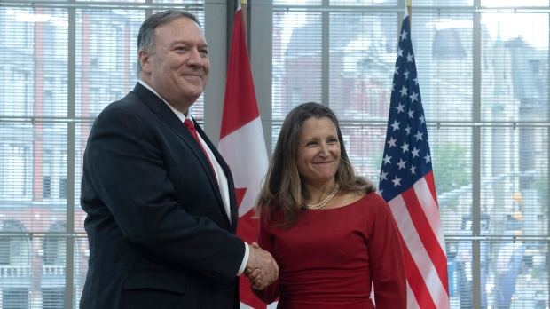 Canadian Foreign Affairs Minister Chrystia Freeland shakes hands with US Secretary of State Mike Pompeo as he lays a wreath at the National War Memorial in Ottawa, Thursday, August 22, 2019. THE CANADIAN PRESS/Adrian Wyld