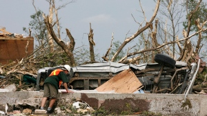 Environment Canada officials inspect the damage in Elie, Manitoba in June 2007 following a tornado. (CP PHOTO/John Woods)