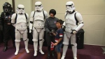 A new Canadian poses for a photograph with stormtroopers at the 25th annual Fan Expo.