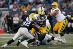 Green Bay Packers' Tra Carson (32) runs against Oakland Raiders' Dallin Leavitt (32) during the first half of NFL pre-season action in Winnipeg Thursday, August 22, 2019. (THE CANADIAN PRESS/John Woods)