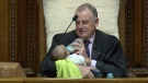 In this Wednesday, Aug. 21, 2019, image from video, New Zealand House Speaker Trevor Mallard bottle-feeds lawmaker Tamati Coffey's baby, Tutanekai Smith-Coffey, while presiding over a debate in parliament in Wellington, New Zealand. (Parliament TV via AP)