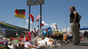 In this Aug. 12, 2019 photo, mourners visit the makeshift memorial near the Walmart in El Paso, Texas, where 22 people were killed in a mass shooting that police are investigating as a terrorist attack targeting Latinos. (AP Photo/Cedar Attanasio)