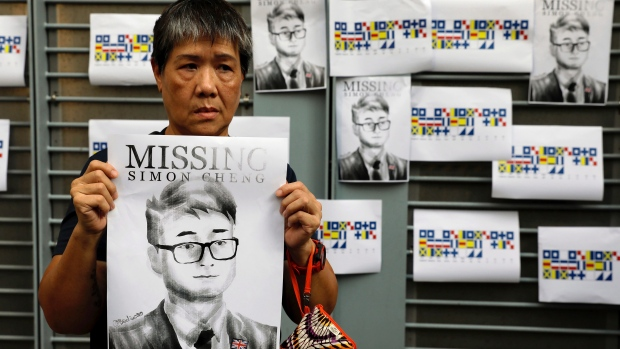A supporter holds a poster outside of the British Consulate in Hong Kong during a rally in support of an employee of the consulate who was detained while returning from a trip to China, Wednesday, Aug. 21, 2019. (AP Photo/Vincent Yu)