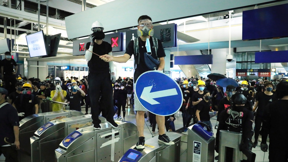 In this Wednesday, Aug. 21, 2019, file photo, demonstrators stand on turnstiles during a protest at the Yuen Long MTR station in Hong Kong. (AP Photo/Kin Cheung, File)