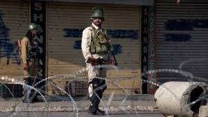 Indian paramilitary soldiers stand guard near a temporary checkpoint during lockdown in Srinagar, Indian controlled Kashmir, Friday, Aug. 23, 2019. (AP Photo/Dar Yasin)