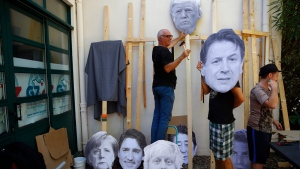 A man fixes an image of President Donald Trump to a wooden pole as he prepares for an anti-G-7 demonstration at a camp near Hendaye, France Friday, Aug. 23, 2019. U.S. President Donald Trump will join host French President Emmanuel Macron and the leaders of Britain, Germany, Japan, Canada and Italy for the annual G-7 summit in the nearby elegant resort town of Biarritz. Other leaders faces on show are from left: German Chancellor Angela Merkel, Canadian Prime Minister Justin Trudeau, Britain's Prime Minister Boris Johnson, Japanese Prime Minister Shinzo Abe, Italian Premier Giuseppe Conte and French President Emmanuel Macron. (AP Photo/Francois Mori)