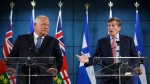 Ontario Premier Doug Ford, left, listens as Toronto Mayor John Tory speaks to media about additional provincial funding for Toronto Police CCTV programs, at the Toronto Police College in Toronto, Friday, Aug. 23, 2019. THE CANADIAN PRESS/Cole Burston