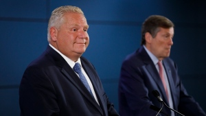 Ontario Premier Doug Ford, left, smiles alongside Toronto Mayor John Tory as the two speak at a press conference to announce additional provincial funding for Toronto Police CCTV programs, at the Toronto Police College in Toronto, Friday, Aug. 23, 2019. THE CANADIAN PRESS/Cole Burston