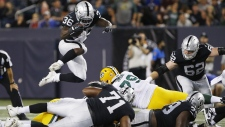 Oakland Raiders' James Butler (36) leaps for yards against the Green Bay Packers during the second half of NFL pre-season action in Winnipeg Thursday, August 22, 2019. THE CANADIAN PRESS/John Woods